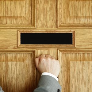 bigstock-businessman-knocking-on-a-door-87571403